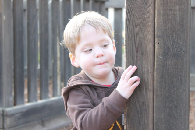 Daniel looking around a corner at Miwok Park.